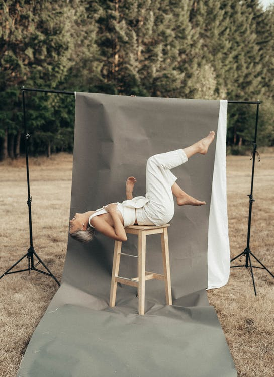 Graceful woman lying on stool in nature