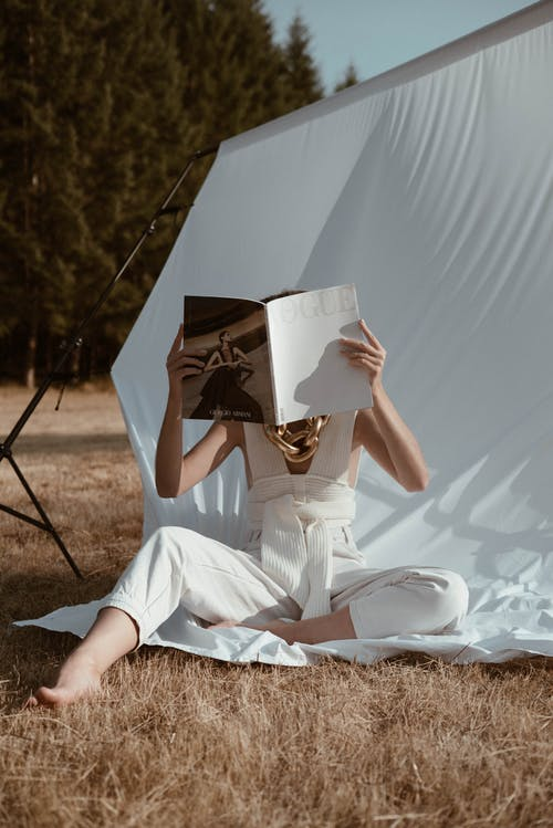 Anonymous woman reading book on white background