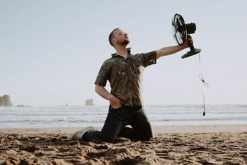 Jovem Com Ventilador Na Praia