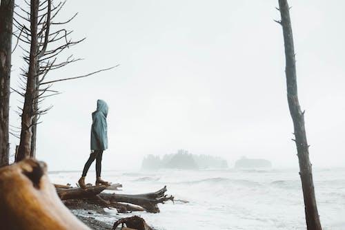 Anonyme Frau, Die An Der Küste Im Bewölkten Steht