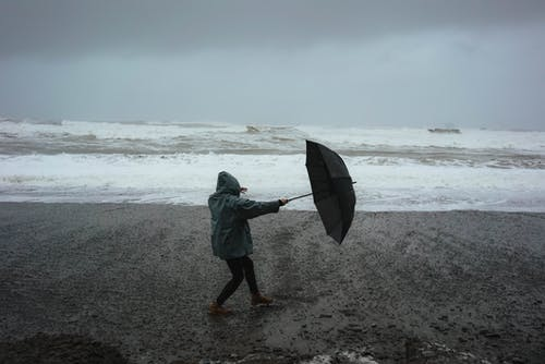 Full body of anonymous person in hood standing in wind with umbrella on sandy shore near stormy sea in rainy weather