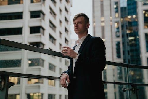 Serious businessman standing near glass fence