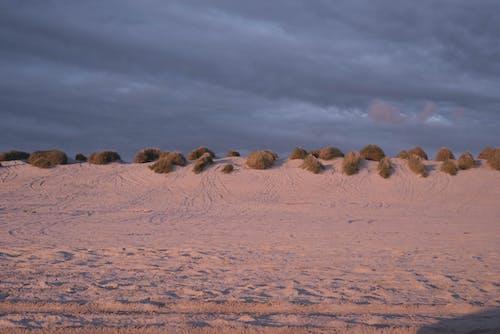 Sandy terrain against cloudy sky