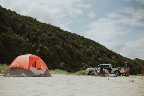 Travelers with car and tent on sandy beach having wild trip in valley with green hills
