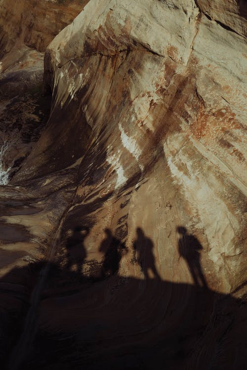 Shadow of travelers on rocky cliff