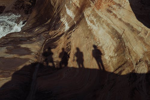People silhouette on high cliff