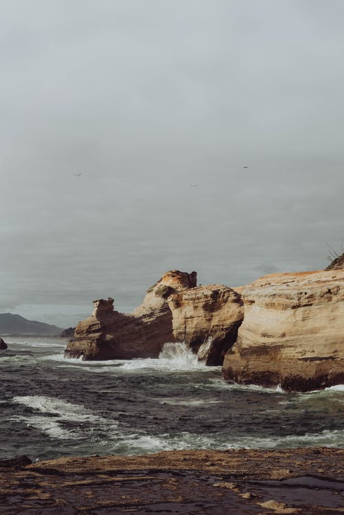 Rough rocky cliff above ocean waves