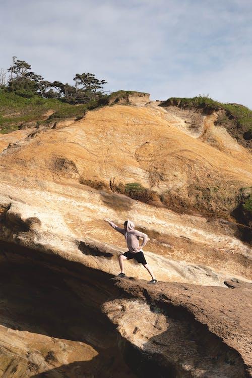 Traveler in hero pose on high cliff