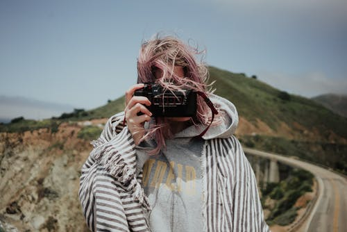 Woman in plaid taking photo in mountains