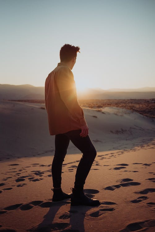 Anonymous man walking on sandy dunes in desert