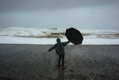 Person with umbrella on shore in storm
