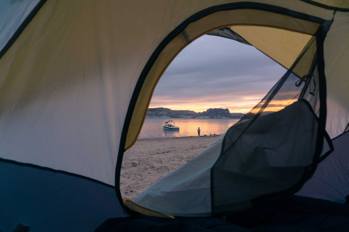 View of sandy beach with calm sea and vessel on water surface through opened tent at sunset time in nature