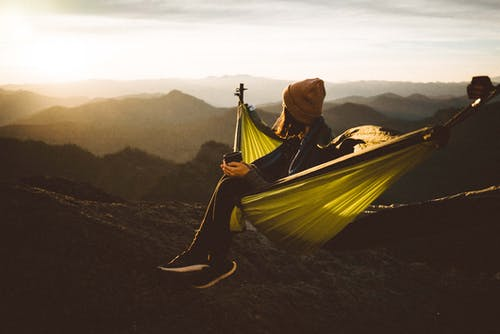 Unrecognizable woman sitting in hammock above mountains