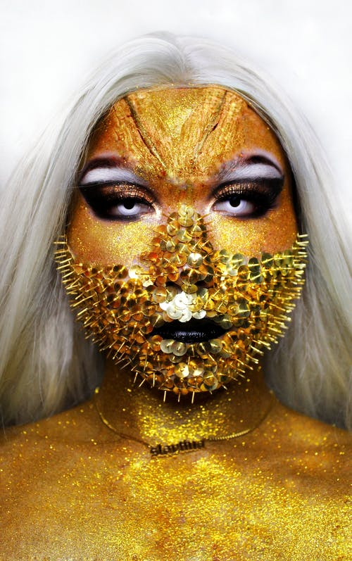 Woman with covered in golden paint
