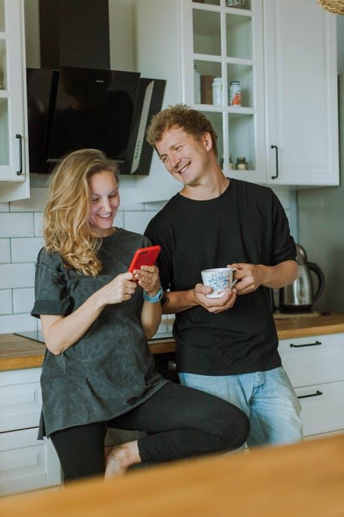 Woman in Gray Shirt Using a Smartphone and Man in Black Shirt Holding a Cup