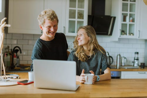 Man Wearing Black Shirt Using a Laptop Beside Woman Holding a Cup