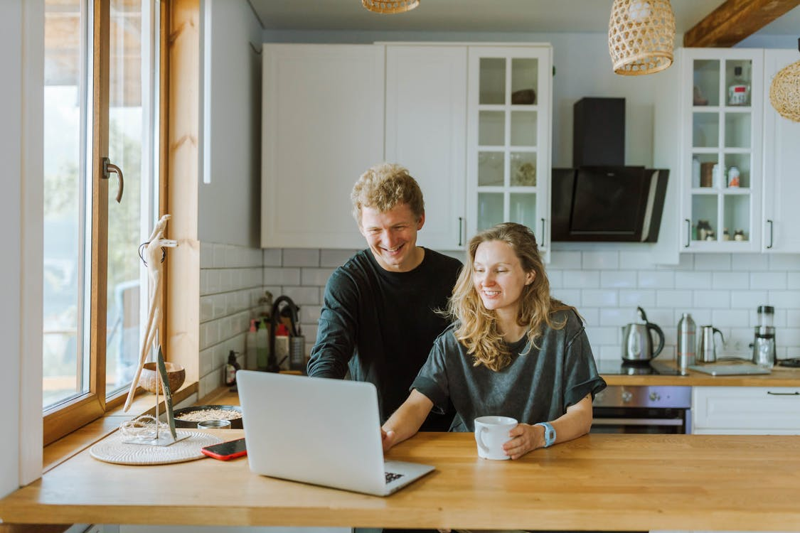 Man and Woman Using a Laptop in the Kitchen Area