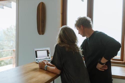 Man and Woman using Laptop on Kitchen Counter Lif by Daylight from Window