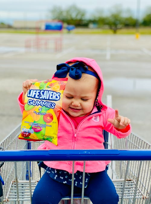 Baby in Pink Jacket Holding Candies