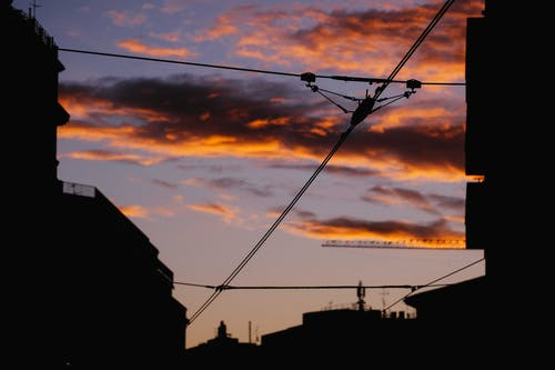 Electrified rails against vibrant sunset in city