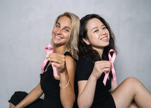 2 Women in Black Tank Top Holding Pink Ribbon