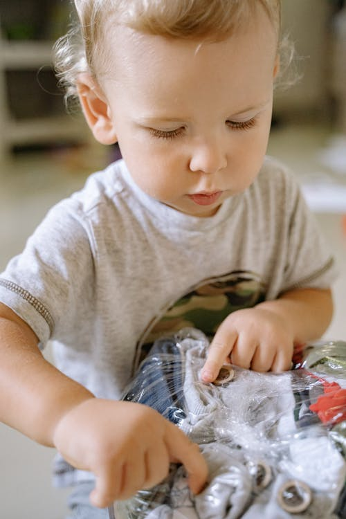 Boy in Gray Crew Neck T-shirt Holding Clear Plastic Pack