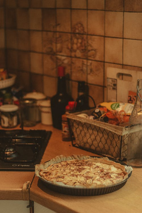High angle of fresh baked pie with apple placed on kitchen table near seasonings and  stove