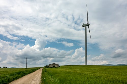 White Wind Turbine on Green Grass Field Under White Clouds and Blue Sky