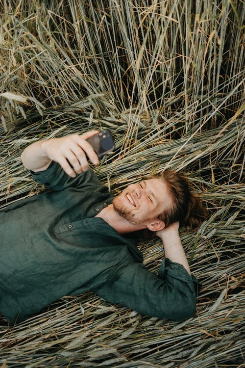 Man in Black Dress Shirt Lying on Dried Grass