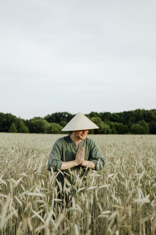 Man in Green Shirt Wearing White Hat Standing on Wheat Field
