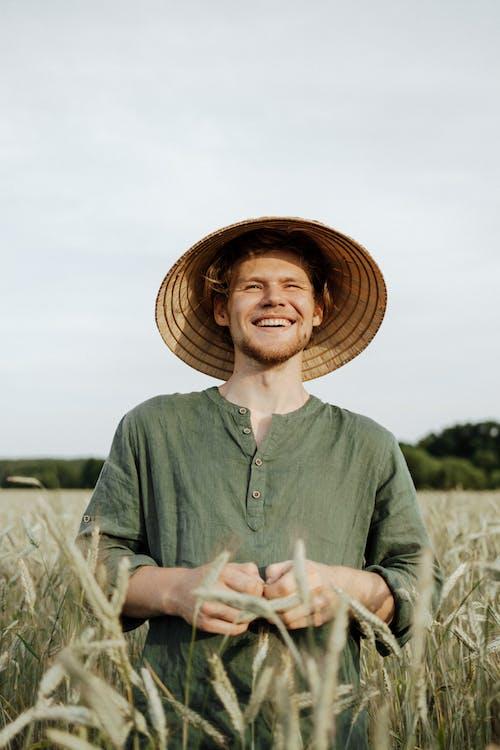 Man in Green Long Sleeve Shirt Wearing Brown Straw Hat