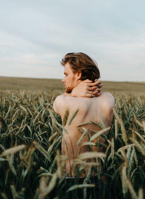 Shirtless Man Standing on Green Grass Field
