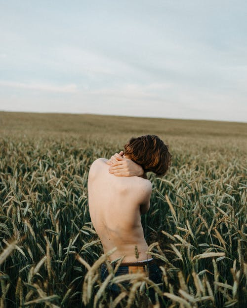 Topless Man in Black Bottoms Standing on Green Grass Field