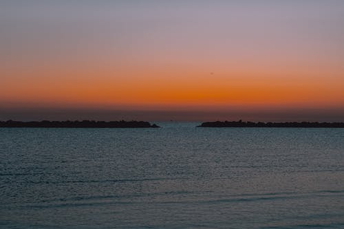 Amazing sunset over rippling sea with breakwater