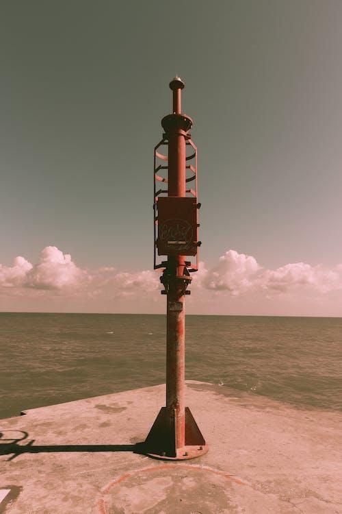 Short lighthouse on concrete platform against rippling sea