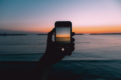 Crop anonymous person taking picture on modern mobile phone of waving sea during picturesque sunset
