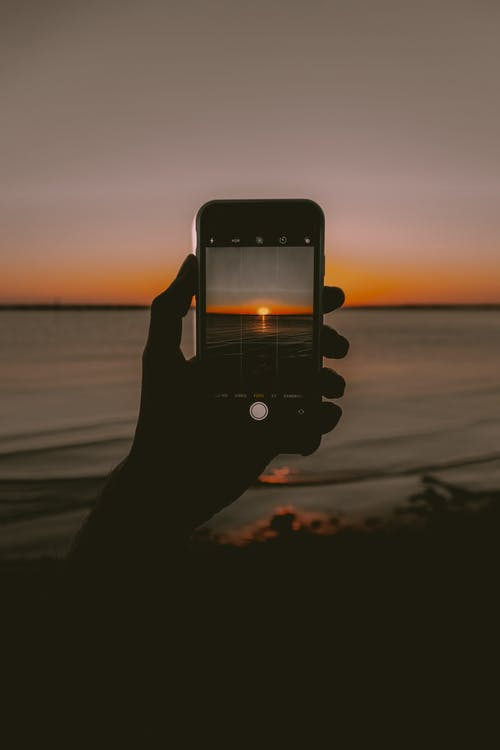 Anonymous person taking photo of sunset over sea on smartphone