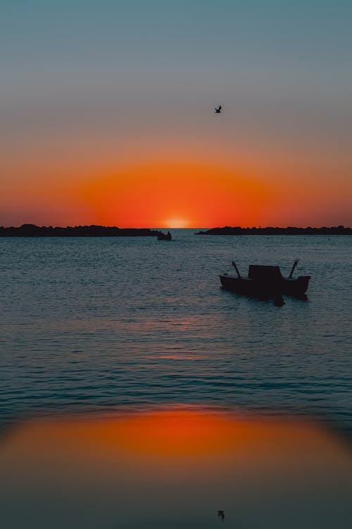 Boat sailing in rippling sea at sunset