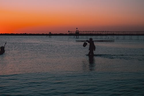 Side view silhouette of unrecognizable man using carrying poles to hold bucket with water while standing in sea against cloudless sunset sky