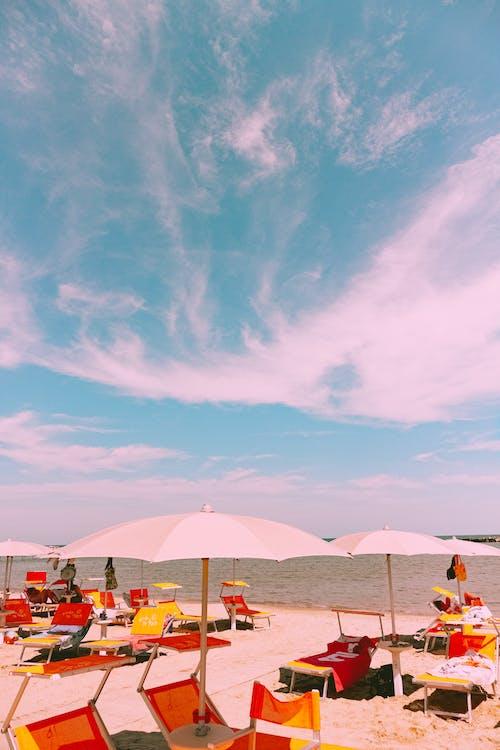 Sunbeds and umbrellas served on sandy beach near wavy sea against cloudy blue sky on sunny summer day