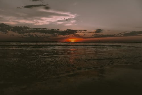 Picturesque scenery of waving ocean washing sandy beach against dark cloudy sunset sky