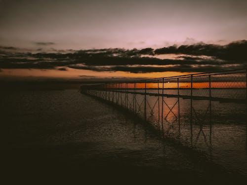 Cloudy sundown sky over pier and sea