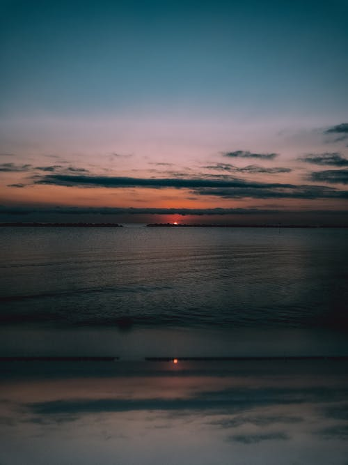 Picturesque landscape of colorful cloudy evening sky with sun setting over calm sea