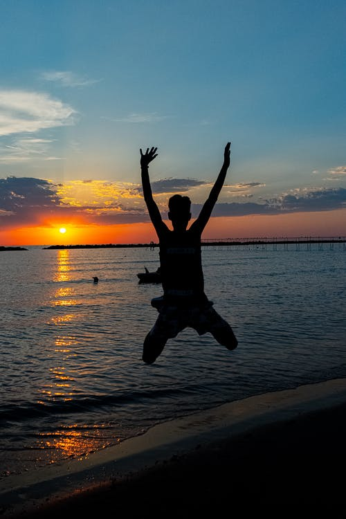 Silhouette of anonymous happy traveler jumping on sandy beach with raised arms against picturesque sunset sky over waving sea