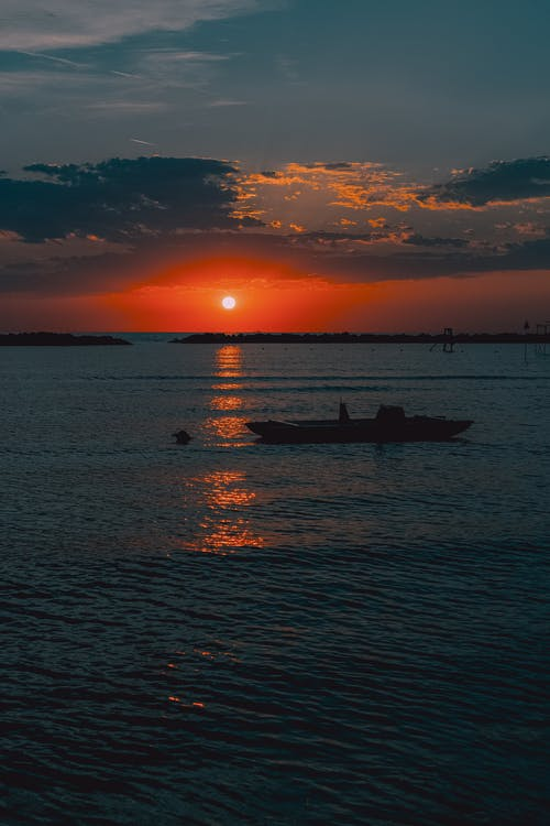 Orange sunset over sea with floating vessel