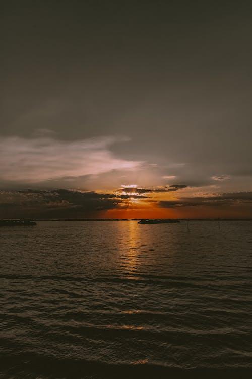 Dark sundown sky over picturesque waving ocean