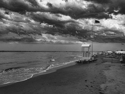 Sandy beach of wavy sea with lifeguard house against cloudy sky