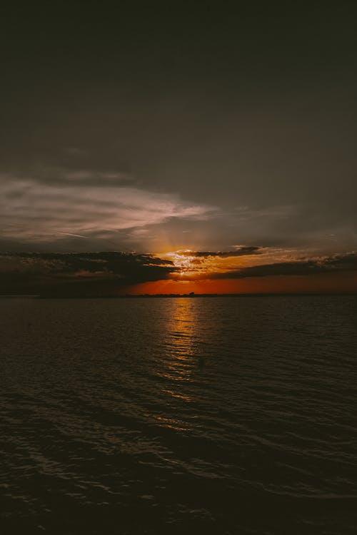 Evening sky with orange sun shining over sea