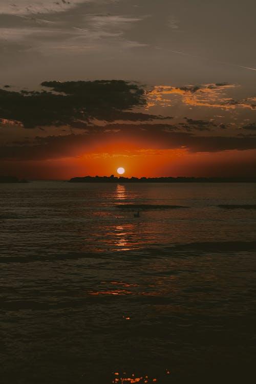 Orange sunset over wavy dark sea