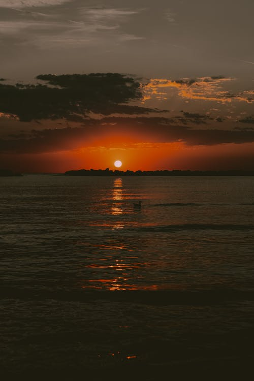 Scenic landscape of cloudy evening sky with vibrant orange sun setting over wavy ocean